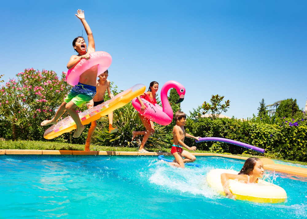 Kids jumping into pool with pool floats