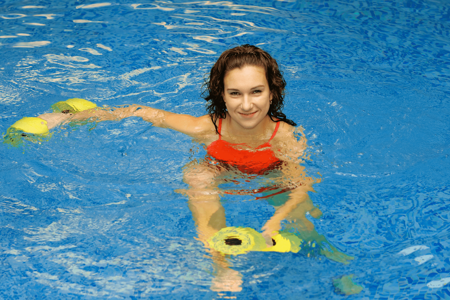 Women with dumbells in the pool