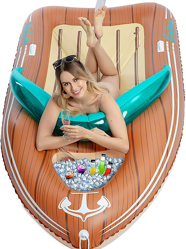 Woman laying on pool float shaped like a boat with cooler
