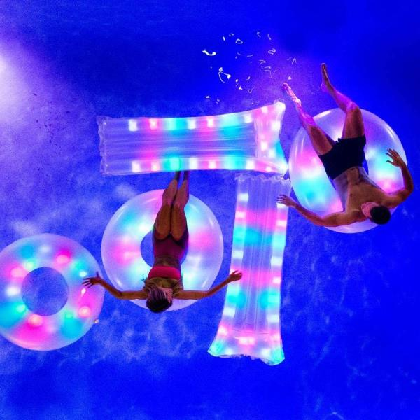 Man and woman floating in lighted pool floats