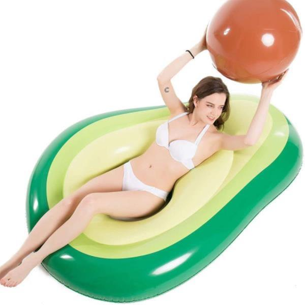 Woman lays in avocado pool float with pit ball